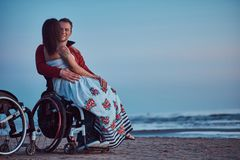 Loving couple, a woman sits on her husband`s lap, resting on a beach against a background of a bright dawn. stock photography