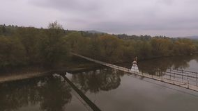 Loving Couple on a Wooden Bridge in the Mountains. Aerial video. Slow motion stock footage