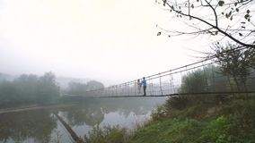 Loving Couple on a Wooden Bridge in the Mountains. Morning fog. Slow motion stock video footage