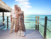 Loving couple on a wooden platform over the sea on the tropical island Stock Images