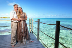 Loving couple on a wooden platform over the sea on the tropical island Royalty Free Stock Image