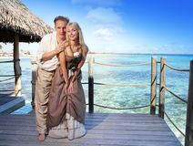 Loving couple on a wooden platform over the sea on the tropical island Royalty Free Stock Photos