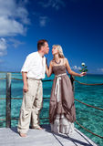 Loving couple on a wooden platform over the sea on the tropical island Royalty Free Stock Photography