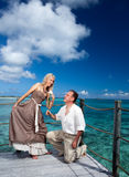 Loving couple on a wooden platform over the sea on the tropical island Stock Image