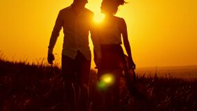 Loving couple - young man and beautiful girl walking at sunset meadow - silhouette. Shot stock video