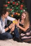 Loving couple of young people  meet New Year or celebrate Christ. Mas at a fir tree with glasses with champagne Stock Image