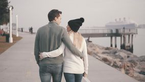 Loving couple of young people are walking in the park. Against the background of a beautiful bay. Pleasant evening near the ocean. Talking and kissing stock footage