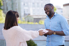 Loving creative girl making a sweet surprise. I got something for you. Lovely pleasant genuine guy feeling sentimental as his girlfriend giving him a present and royalty free stock photos