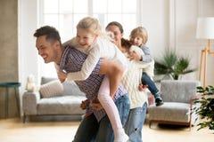Loving dad piggybacking little daughter playing with family at h. Happy loving dad piggybacking little daughter playing with family at home, smiling parents Royalty Free Stock Photos
