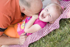 Loving Dad Tickles Daughter in Park Stock Photography
