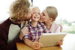 Loving daughter. Affectionate parents kissing their cute daughter on cheeks while spending time together stock photo