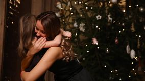 Loving daughter hugging her mother against the Christmas tree background stock video