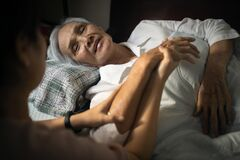 Free Loving Daughter Is Talking And Visiting Her Sick Elderly Mother Lying In Bed,caregiver Woman Holding Hand Of Asian Old Patient And Stock Photos - 181997813