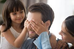 Loving daughter and mother cover male eyes stock photo