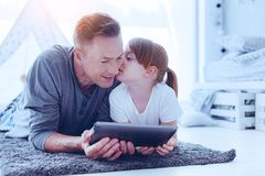 Loving daughter whispering something to her dad. Secret information. Mature men looking at a screen of his digital tablet with a slight smile on his face while Royalty Free Stock Photo