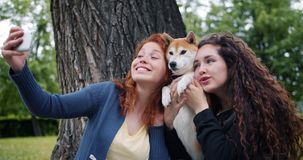Loving dog owners girls taking selfie with pet in park using smartphone camera
