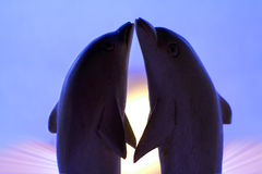 Loving dolphins. Two plastic dolphins in love on sunrise background royalty free stock images