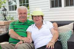 Loving elderly couple relaxing on an outdoor patio Stock Images