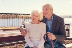 Loving elderly couple sitting together on the bridge stock photography