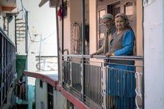 Loving elderly couple standing outside house hand holding railing at Saharan town, Himachal Pradesh. Stock Image