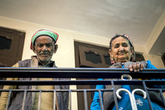 Loving elderly couple standing outside house hand holding railing at Saharan town, Himachal Pradesh. Royalty Free Stock Photos