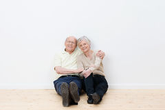 Loving elderly couple in their new home. Sitting side by side on the bare wooden floor smiling in satisfaction Stock Images