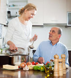 Loving elderly senior and mature wife cooking together royalty free stock photography