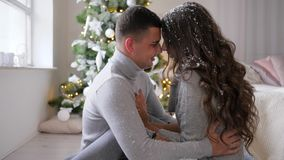 Loving emotions, bright artificial snowflakes fall on hair of two lovers in the room near the Christmas tree. Loving emotions, bright artificial snowflakes fall stock footage