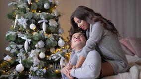 Loving emotions, young woman sit on couch and hugging spouse near to fir tree on eve of Christmas. Loving emotions, young woman sit on couch and hugging spouse stock video footage