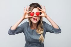 Loving eyes. Beautiful caucasian young woman holding two valentine hearts in front of her eyes like glasses with sensual royalty free stock photo