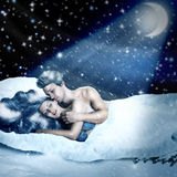 Loving fairy couple in a bed of snow Royalty Free Stock Image