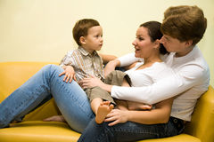 Loving family. Young couple with their little son on the yellow sofa Stock Images
