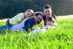 Loving Family. Father playing with children.  Family is lying down outside in a grassy field Stock Photography