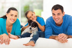 Loving family bed. Loving young family lying on bed at home with their pet dog royalty free stock photos