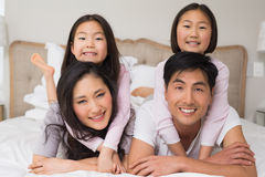 Loving family of four lying in bed at home. Portrait of a loving family of four lying in bed at home stock photos