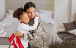 Loving family happy being reunited. Nothing feels better than this. Admirable fearless attractive women and her child hugging while sitting on a bed and looking royalty free stock photos
