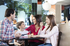 Loving Family Having Ice Creams At Table In Parlor. Happy loving family having ice creams while sitting at table in parlor stock images