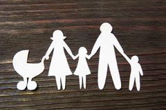 Loving family holding hands. Paper figures on a background of mahogany. Royalty Free Stock Image