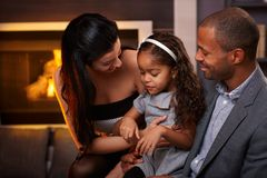 Loving family at home. Beautiful loving family sitting in living room by fireplace, smiling stock photos