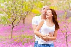 Loving family hugging in spring park Stock Photo