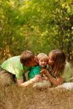 Loving family kiss. Mother and father kissing little son in summer nature Stock Photos
