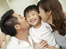 Loving family. Little boy kissed by mother and father Royalty Free Stock Images