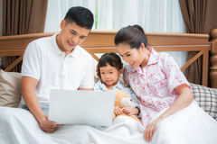 Loving family looking at a laptop lying down on bed Royalty Free Stock Photography