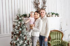 Loving family Merry Christmas and Happy New Year. Cheerful pretty people. Mom and dad hugging little daughter . Parents. And baby child having fun near royalty free stock photography