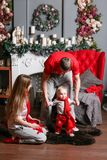 Loving family Merry Christmas and Happy New Year. Cheerful pretty people. Mom, dad and little baby son . Parents and. Child having fun near stock photo