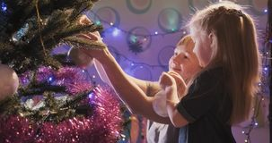 Loving family. Mom and daughter decorate the Christmas tree indoors. Loving family stock video