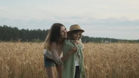 Loving family, older sister caring, playing, looking with younger girl. Field of wheat summer nature background stock video footage