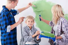 Loving family painting wall together. Image of loving family painting wall together stock photo