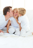 Loving family playing sitting on a bed Royalty Free Stock Photography