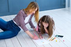 Loving family relationship involvement kids hobby. Loving family relationship. mothers involvement in kids hobby. mom and daughter drawing together at home royalty free stock images